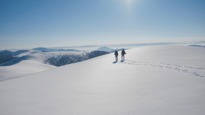 two winter mountain hikers on sunny day